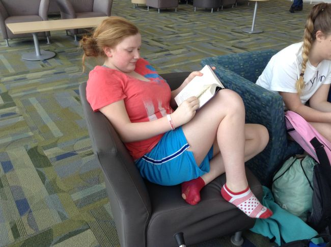 Freshman Shannon Kelly kicks off her shoes and gets comfy with a book in Town Hall at lunch.
