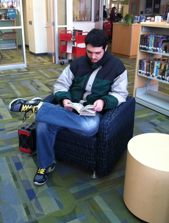 Sean Romiti-Schultze '16 kicks back in the stacks to read some Anime in the library.