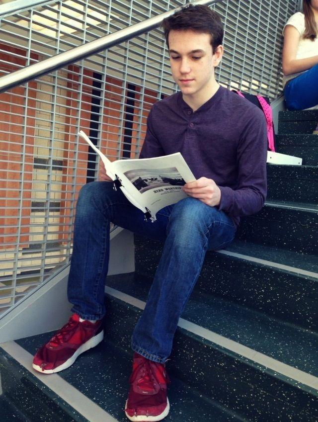 """Adam Voight  '17  reads the play, """"Hero Worship"""" by Joe Calarco on the steps in front of the auditorium."""
