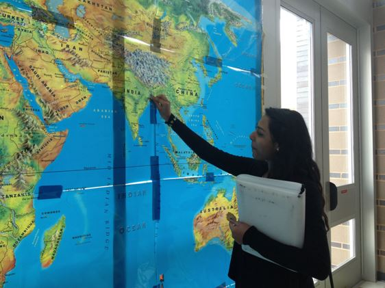 Senior Angelica Gomez reads the Wakefield Heritage week map. Students flagged places all over the world where they have come from.