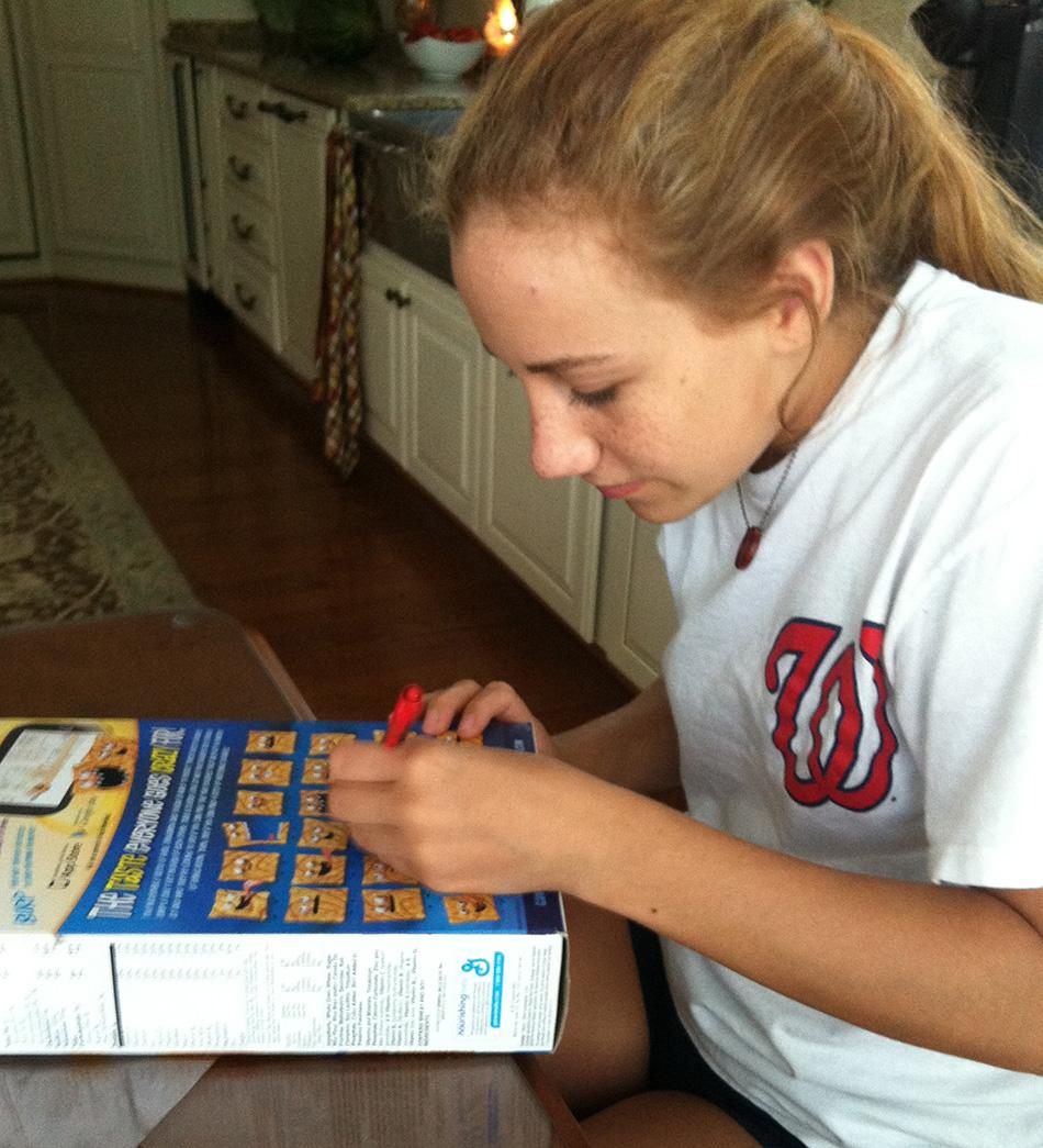 Sophomore Olivia Ceccato reads and completes the games on the back of her Cinnamon Toast Crunch cereal box.