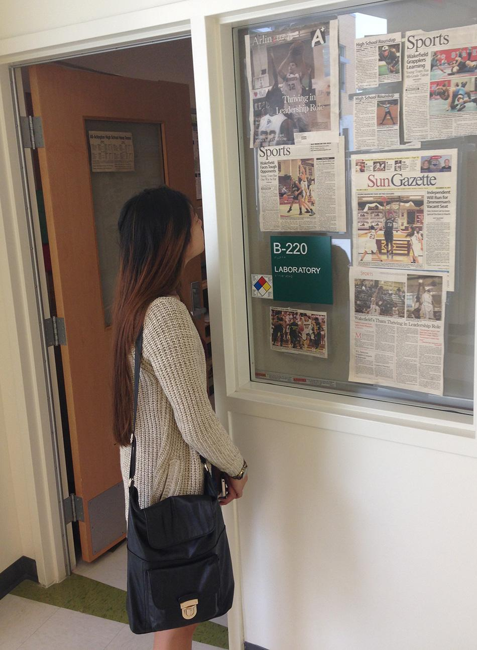 Senior Cathleen Madlansacay reads the sports clippings that Mr. Harris has posted outside his room.
