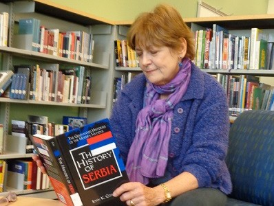 Linda, one of the visiting alumna, flips through a book on Serbian history in the new library.