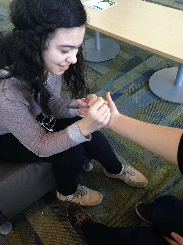 Karla Ortez '17, with pen in hand, hands important information to her friend.