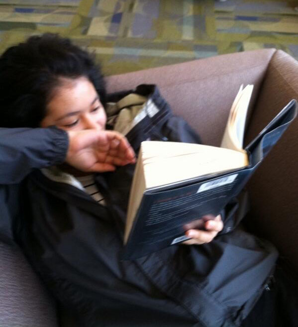 Sophomore Keidy Enamorado hides her smile as she gets to the good part in her book.