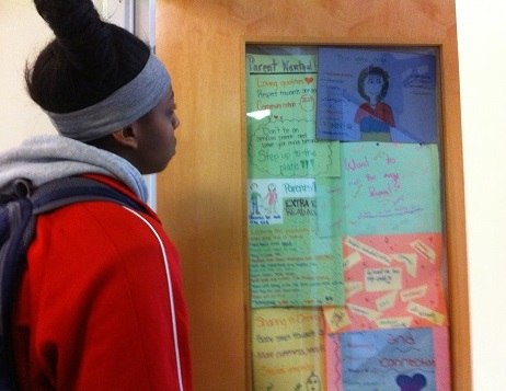Michelle Noel '14 kills time in between classes reading the cards that are taped to the Food and Fitness classroom, A-212.