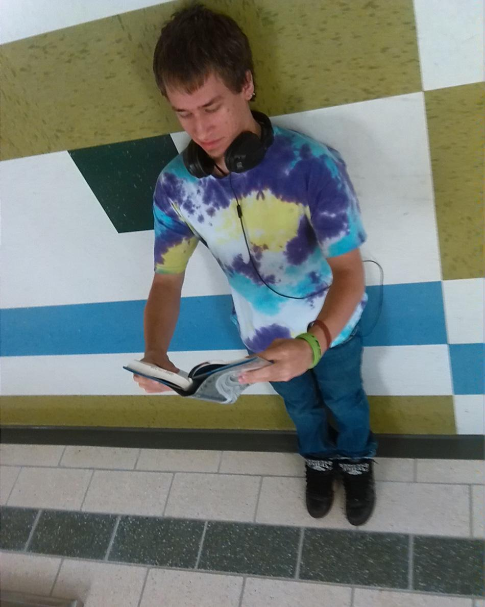 Sophomore Christian Ward reads a new dystopian novel during lunch. It is so good that he is standing on the wall. How did he do that?