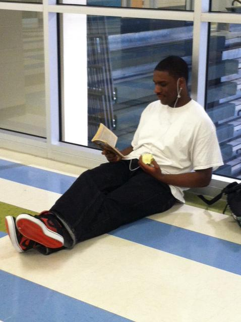 Senior Davone Roseboro enjoys lunch and a book in the hall by the new gym at lunch.