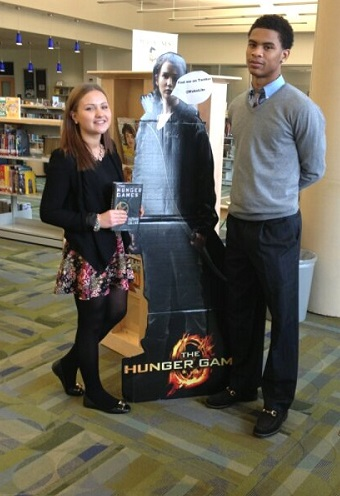 The two article authors pose with the famous Katniss Cut Out in the library before surveying the students for 2013 movie picks.