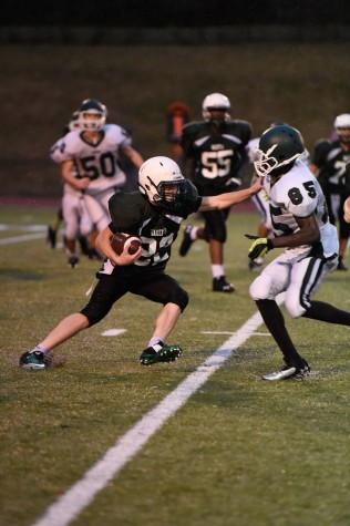 Freshman Running Back Isaiah Calfee stiff arms a Falls Church defender in their win against Falls Church.