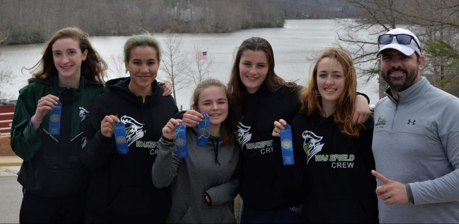 The Women's Junior Four posing with their first place ribbons and coach, James Augone.