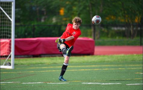 Alex kicks the ball upfield.