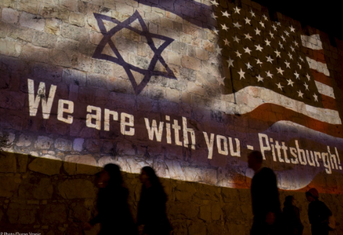 People walk past a projection on the Old City wall in Jerusalem, Sunday, Oct. 28, 2018 in a commemoration of the victims of a deadly shooting at a Pittsburgh synagogue.