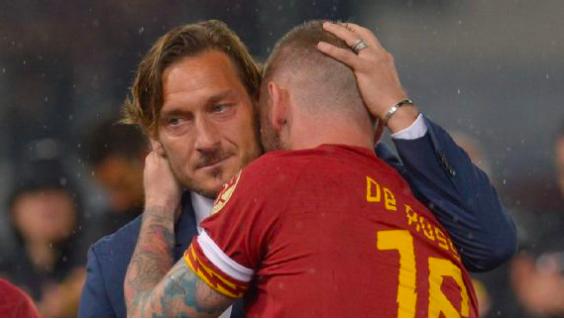 Totti hugging former Roman captain De Rossi.