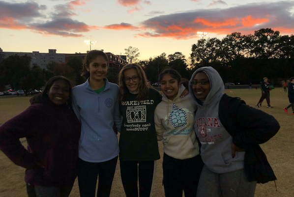Cayla, Tara, Charlotte, Murchana, and Farah smile as the sun sets behind them on another great game.