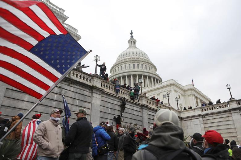 Supporters of President Trump scale the walls of the Capitol Building, January 6.